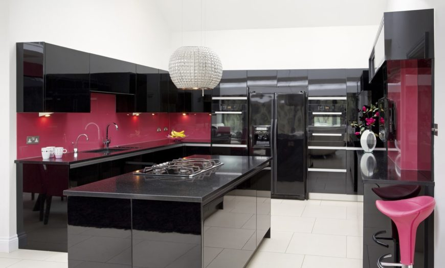 Luxurious kitchen showcases magenta backsplash and black cabinetry. It has a black breakfast island with built-in cooktop lighted by a chandelier.
