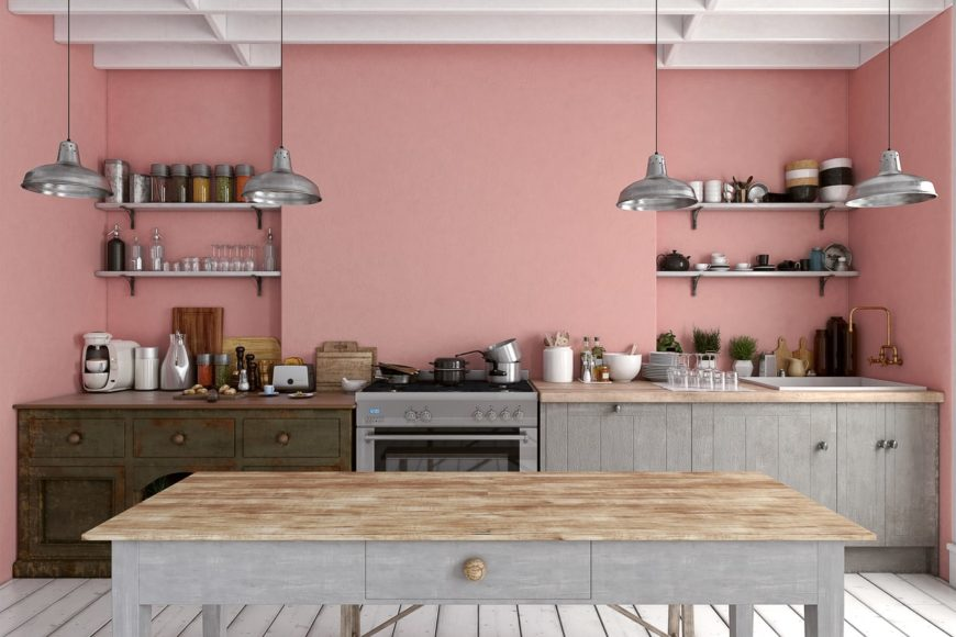 A salmon pink kitchen with white wood beam ceiling and wood plank flooring. It has a wooden table across the kitchen counter lighted by silver pendants.