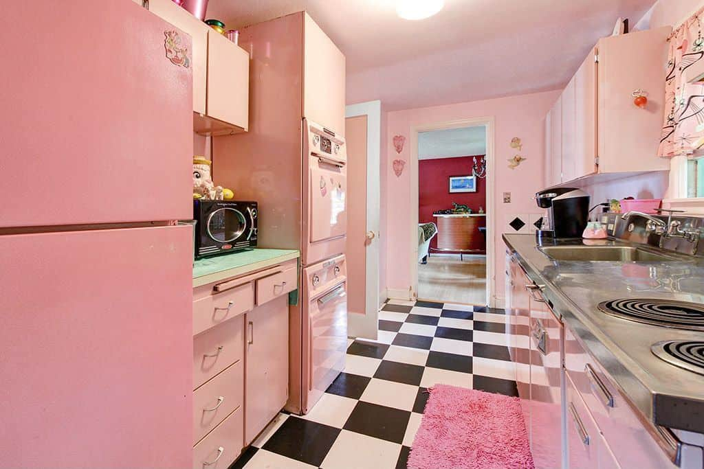 Galley kitchen featuring light pink cabinetry and stainless steel counter fitted with a sink and cooktop. It has checkered flooring topped with a pink shaggy kitchen rug.