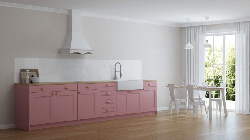 Spacious kitchen features baby pink cabinetry with a wood countertop and white tiles backsplash. It includes a dining space near the floor to ceiling glass window.