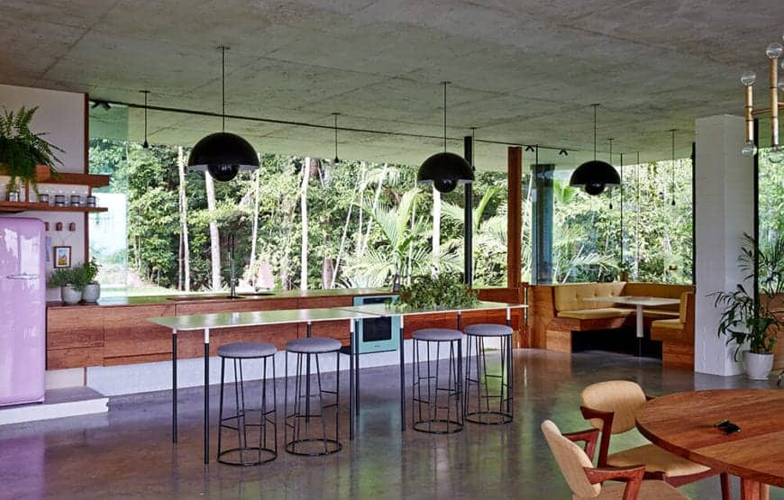An open kitchen with glazed windows overlooking the enchanted forest. It includes lengthy high tables with stool bars lighted by huge black pendants.