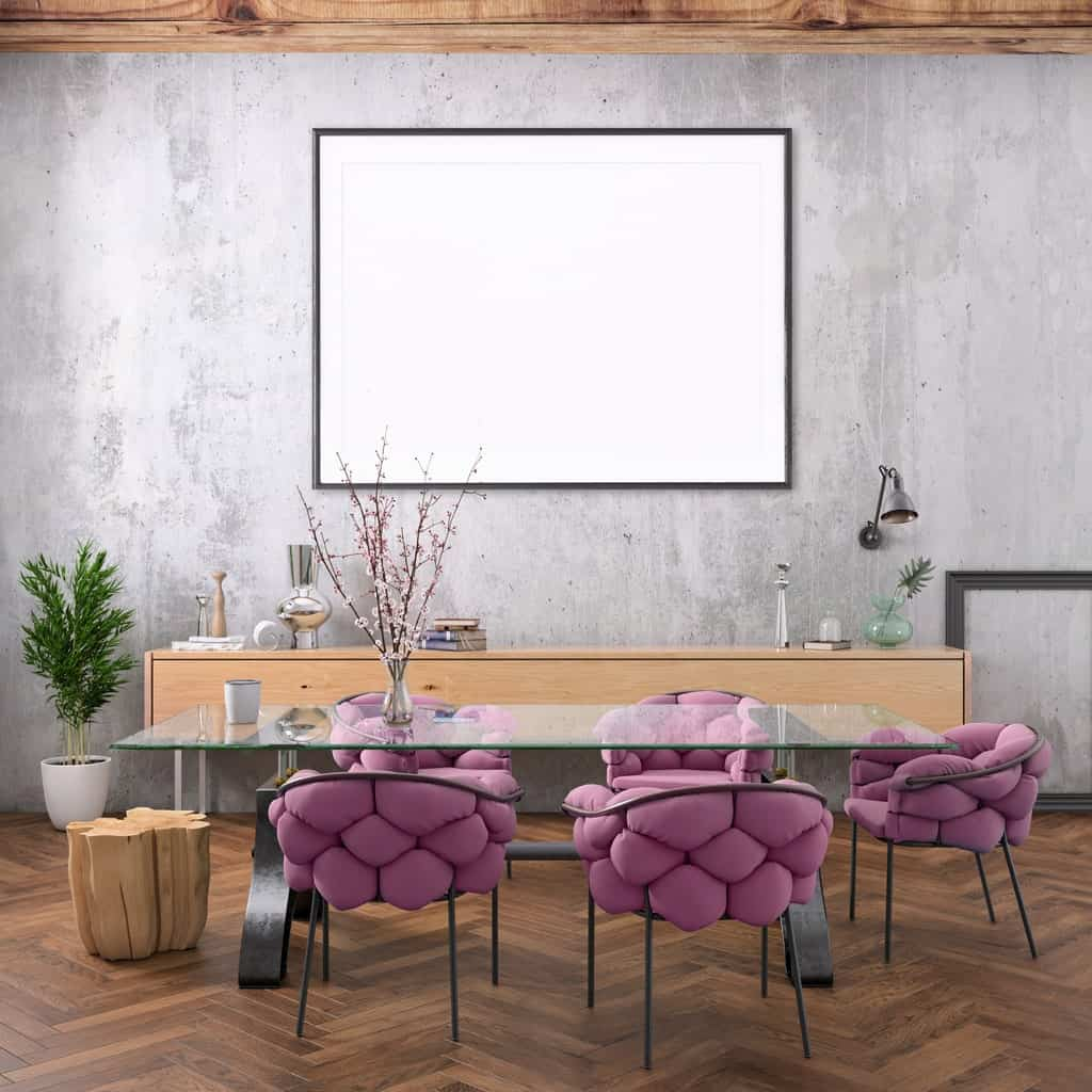 A stylish dining room with bare walls, hardwood floor, a long glass table, statement purple chairs, and simple rustic accents.