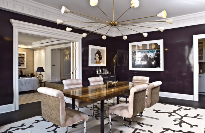 A posh dining area with dark purple walls, a rectangular wooden table with six upholstered chairs, a statement chandelier, and an abstract print rug.