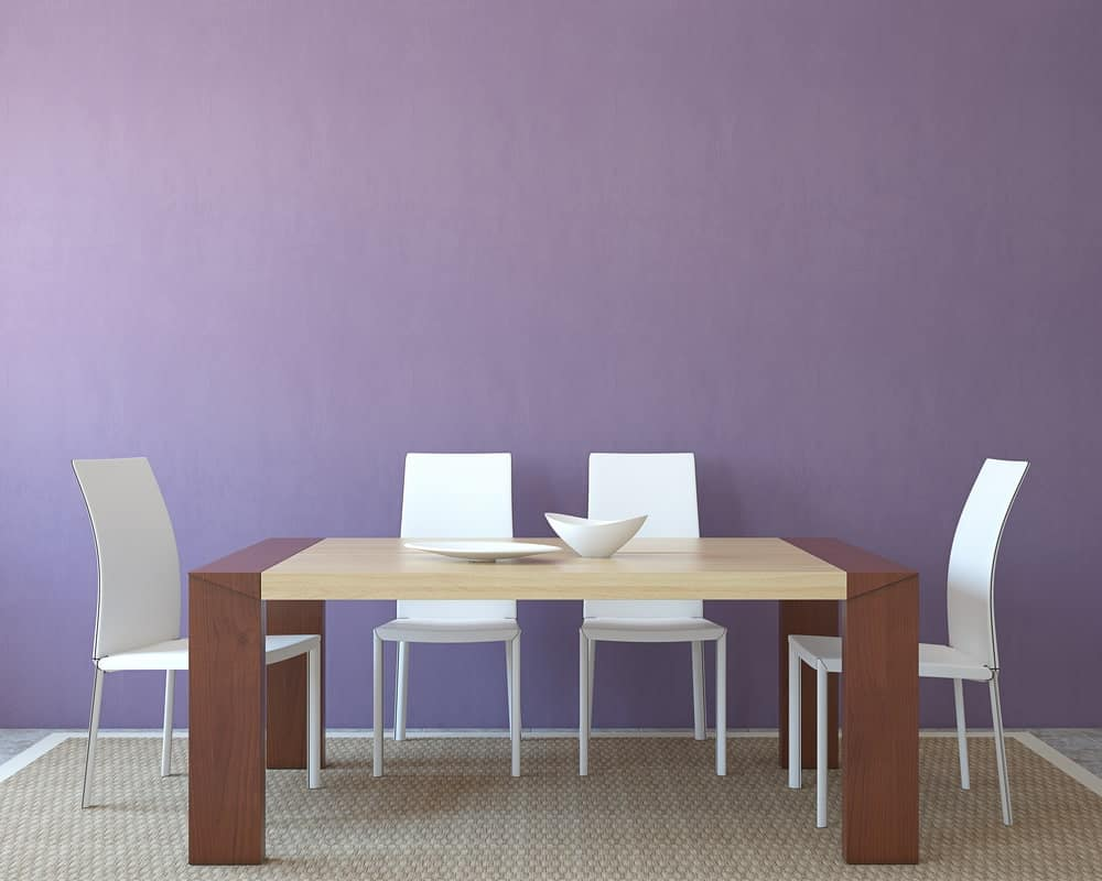 A minimalistic dining area with pastel purple wall, rectangular wooden table for four, white chairs, and a rustic rattan rug.