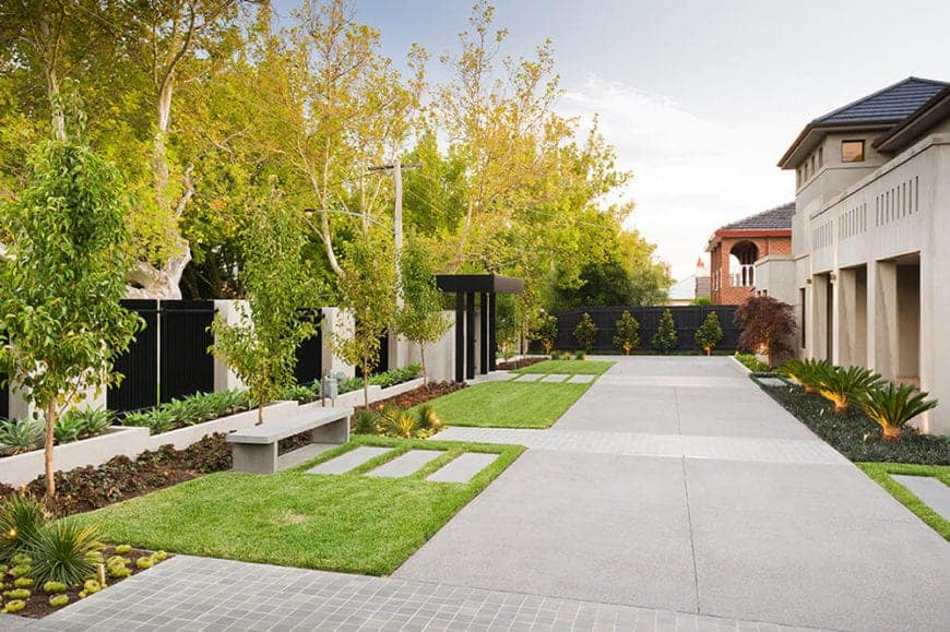A backyard featuring parallel stone pathways over a green luscious lawn, concrete bench, series of plants and concrete plant box on the side of the perimeter wall.