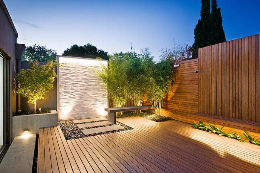 Wooden wall and deck with three rectangular stepping stones over gravel leading to a white water wall that adds elegance to this yard. Bamboo grass and a plant on a concrete planter box highlight the lovely water wall.