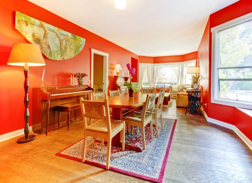 Antique wall art is fixed above the upright piano that's lighted by a traditional floor lamp with an interesting base. Across it is a wooden dining set that sits on a classic red rug over the hardwood flooring.