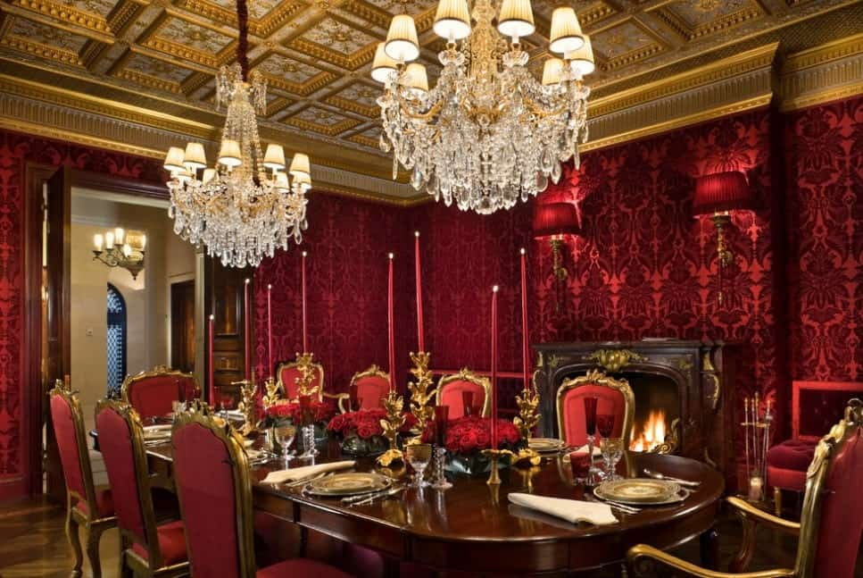 Red and gold are the dominant colors in the palette for this formal traditional dining room. The fireplace with gilded antique mantel fronts the antique eight-seater red cushioned chairs and oval long table, with gilded candelabras, crystal glasses, precious china, and silverware shines as bright as the two traditional crystal chandeliers hanging from a gold-accented coffered ceiling while the red sconces matched the wallpapered walls.