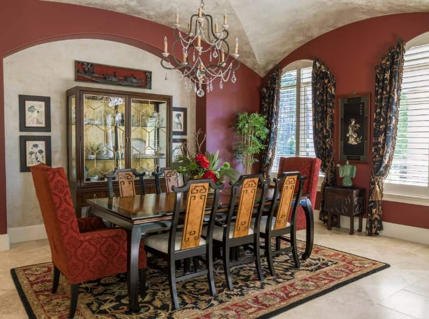 The Asian inspired dark wood dining set coordinates perfectly with the framed art pieces on the walls, Indian end table with elephant carvings, jade figurine. This red dining room is illuminated by the arched windows with custom curtains, hanging chandelier from the domed ceiling and also matches well with the antique rug, and beige marble floor.