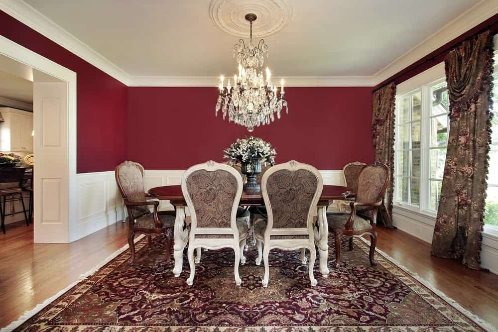 Yet another opulent room with a dining set that gives off a Renaissance vibe, the chandelier hanging from a detailed white ceiling showcases old world decadence and is the perfect traditional accent to this darker toned red dining room with hardwood floors, paisley print upholstered Victorian highback chairs, antique rug, and floral curtains.