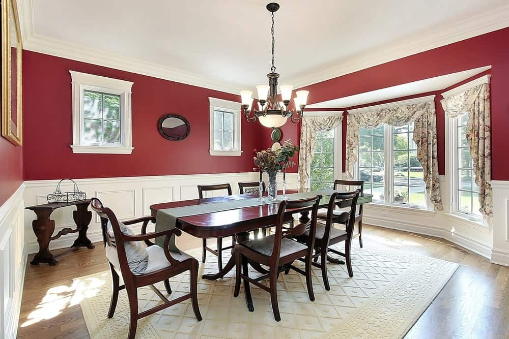 Cozy open red dining room that has a massive white bay and paneled windows with floral swag curtains to let the natural light in is decorated with a heavy six-seater dining set, antique wood side table and an off white intricately patterned rug to protect the hardwood floors from scraping.