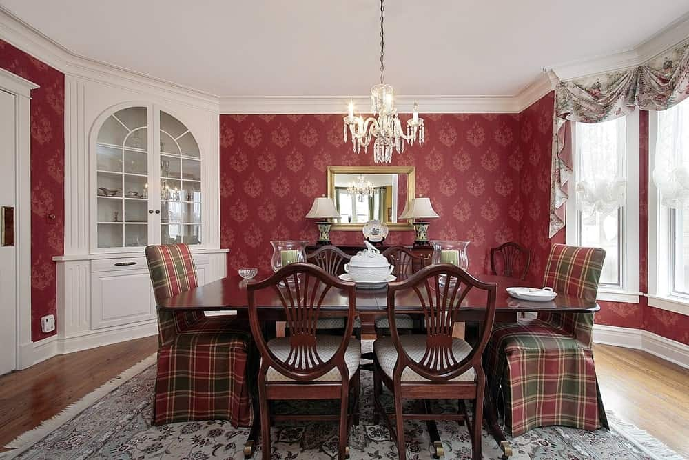 Cozy enclosed red dining room with white crystal and china built-in cabinet, hardwood floors, white molding, white paneled casement windows, graceful white lace, and printed curtains, antique rug, crystal chandelier, gilded mirror, desk lamps, glass candle holders, porcelain centerpiece in a six-seater mixed tartan covered and wood chairs and table.
