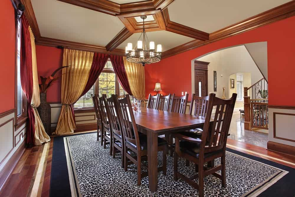 The geometric coffered ceiling in this warm toned red dining room is not the only highlight, an animal print rug covers a random patterned hardwood floor, two-colored floor length curtains, wood vase in the corner, hardwood eight seater dining set, wrought iron 9-light chandelier featuring an intricate interweaving pattern and an antique finish.