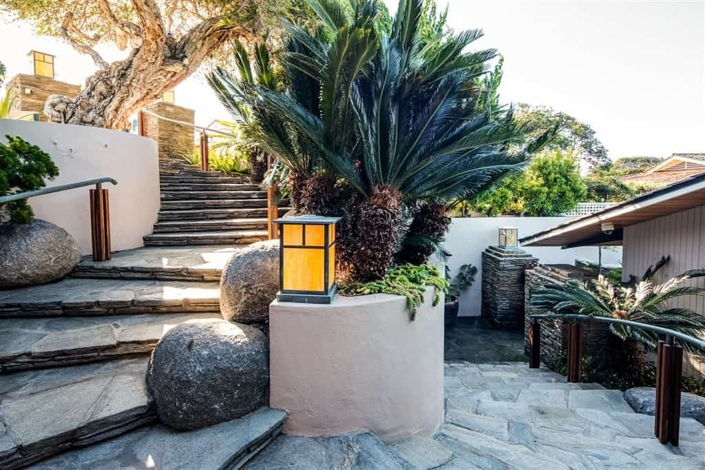The stone staircase spotted with boulders, surrounded by tropical plants, and bookended by a pair of stone columns replicates the rocky coastline and the steep slope of its topography.