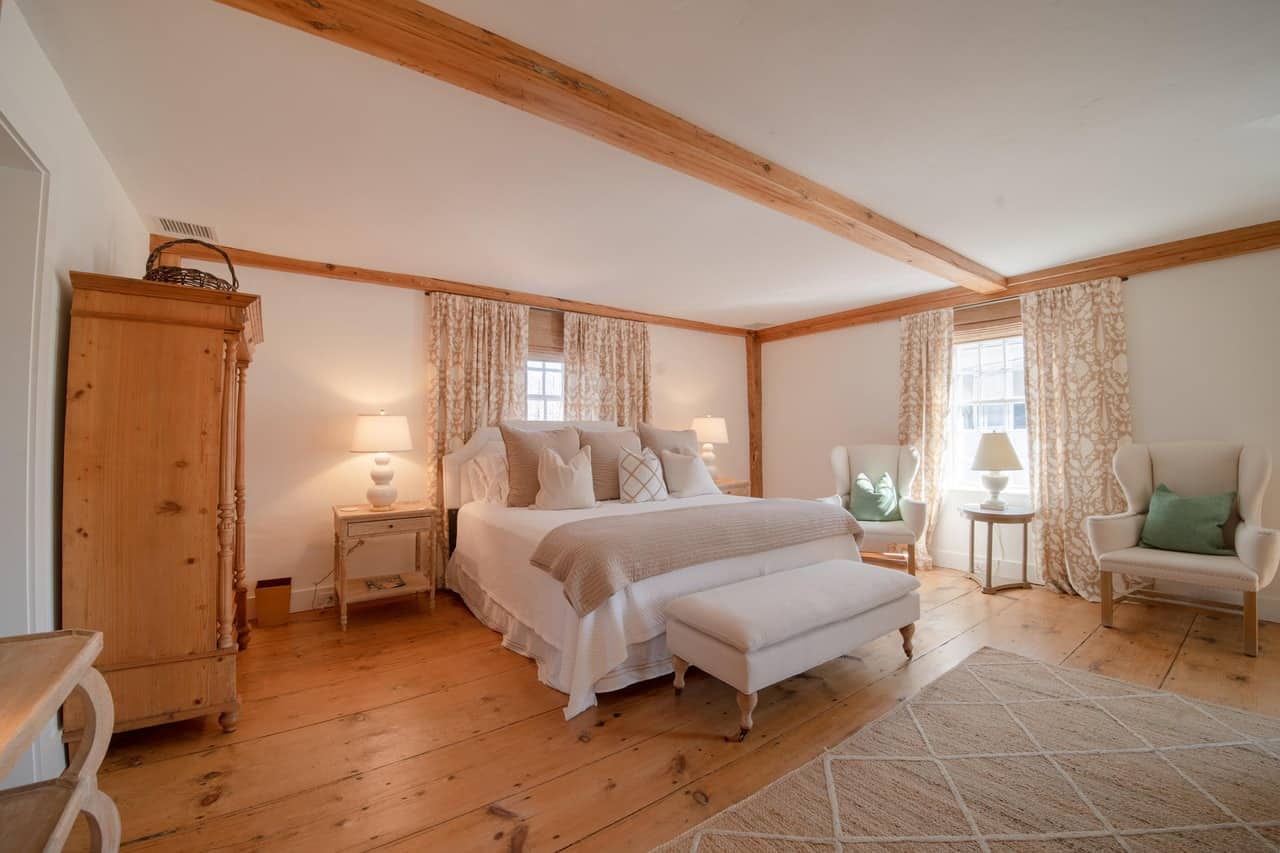 Here's a primary bedroom with white walls, ceiling, bed and ottoman with light natural stained hardwood flooring and ceiling beams.