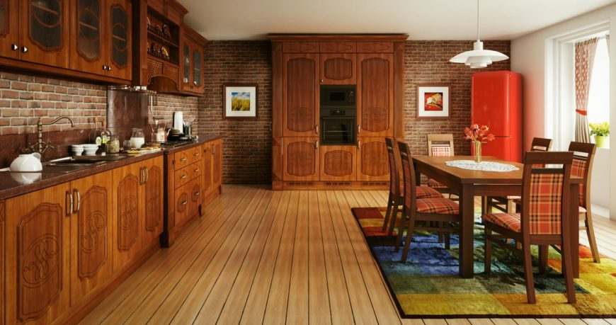 Large dine-in kitchen featuring a rustic dining table and chairs set on top of a rug covering the hardwood flooring. The brick tiles walls add style to the home.