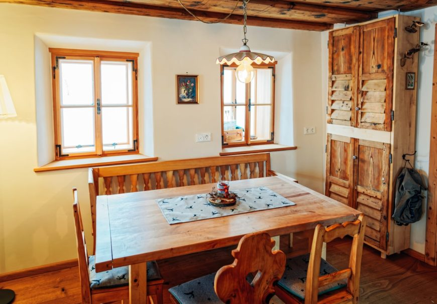 A dining room featuring a rustic dining table set along with a rustic cabinetry. The ceiling is also in rustic style and has beams.