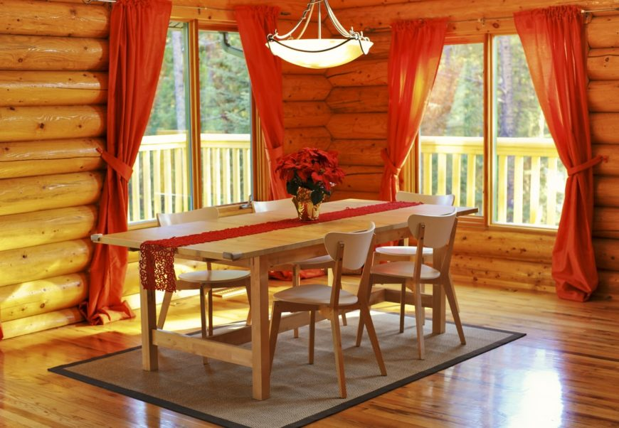 Spacious rustic dining room featuring a wooden dining table and chairs set lighted by a charming pendant lighting.