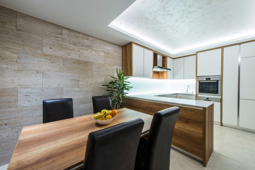 A dine-in kitchen featuring a tray ceiling and tiles flooring. The room has a dining table set for four.