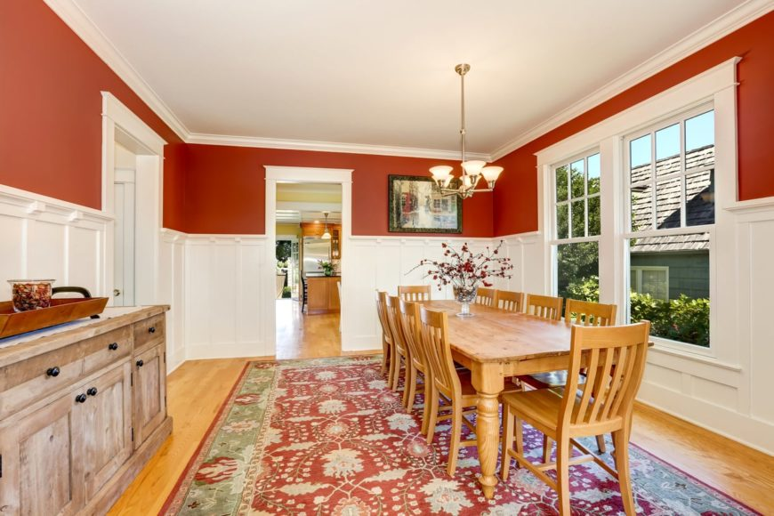 A dining room featuring a rustic dining table and chairs set surrounded by white and red walls. There's a large area rug covering the hardwood flooring. The room is lighted by a fancy chandelier.