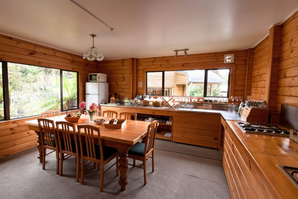 A dine-in kitchen featuring a rustic dining table set situated on the gray carpet flooring.