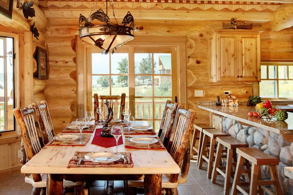 A dine-in kitchen featuring a rustic dining table and chairs set lighted by a fancy pendant light, along with a breakfast bar.