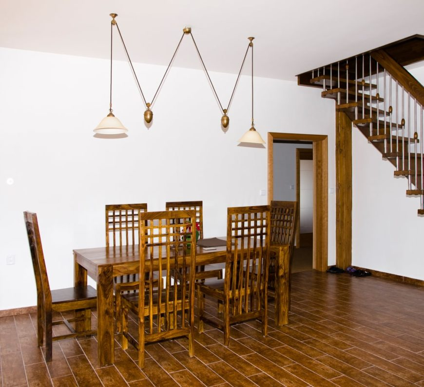 A rustic dining table and chairs set surrounded by white walls and tiles flooring and lighted by fancy ceiling lights.
