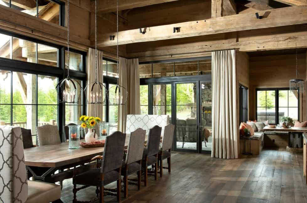 A rustic home featuring hardwood flooring and a tall ceiling with exposed beams. The dining table set looks very classy, lighted by gorgeous pendant lights.