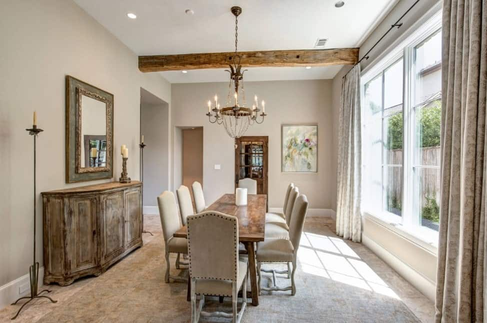 This dining room offers rustic furniture, along with a rectangular dining table set lighted by a gorgeous chandelier.