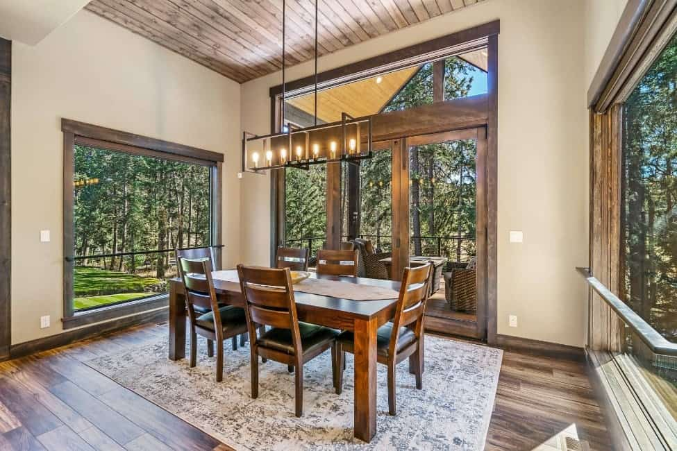 A dining room featuring hardwood flooring topped by a rug, along with a tall rustic ceiling. There's a rectangular dining table set lighted by a fancy ceiling light.