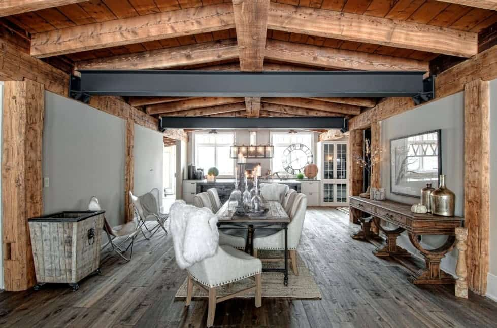 This dining area features a classy dining table and chairs set under the rustic ceiling with exposed beams.