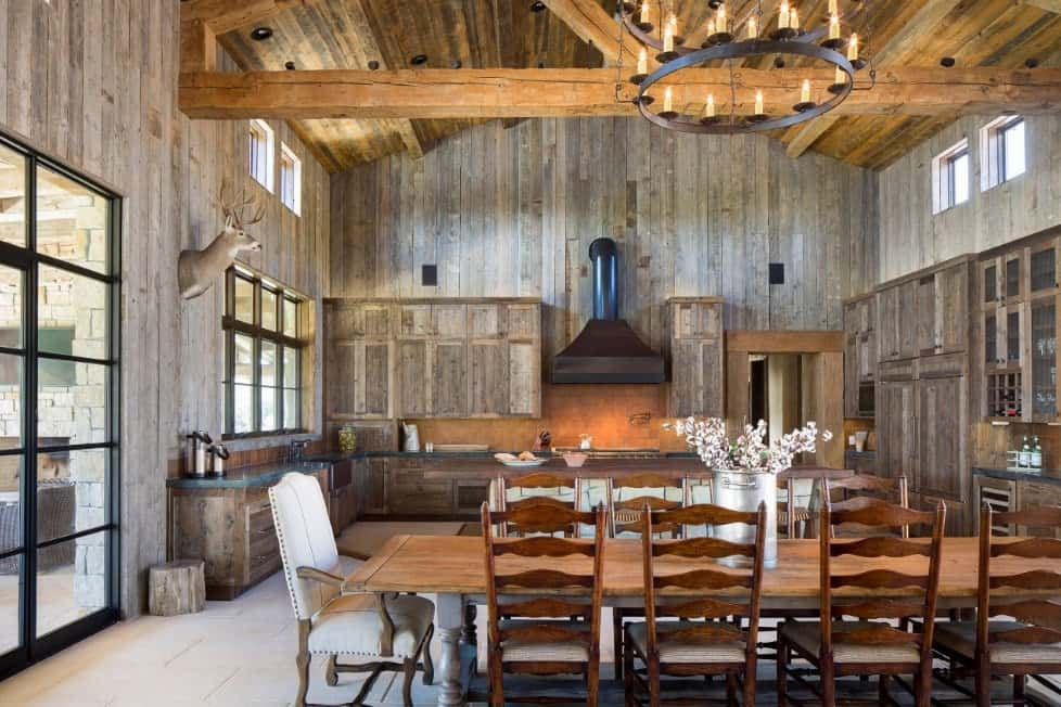 A large rustic dine-in kitchen featuring a rectangular dining table and chairs set lighted by a fancy ceiling light hanging from the tall ceiling.