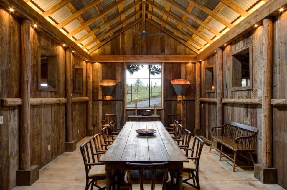 Rustic dining room featuring a rectangular dining table set for 10, under the tall vaulted ceiling with exposed beams.
