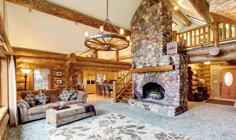 Huge living area with stylish carpet flooring topped by a rug. The room has a comfy couch along with a stone fireplace.