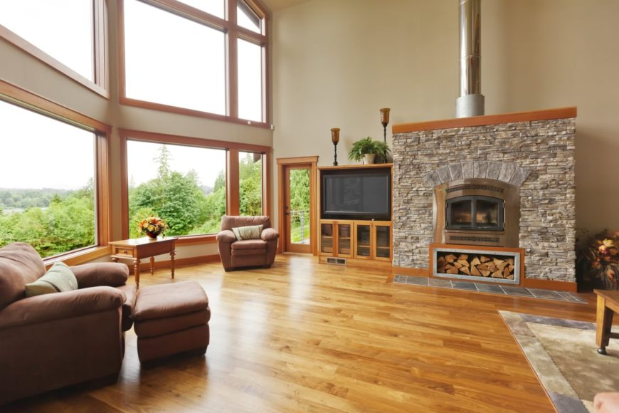 Spacious living room with brown leather seats a TV and a fireplace, along with hardwood flooring topped by a rug.