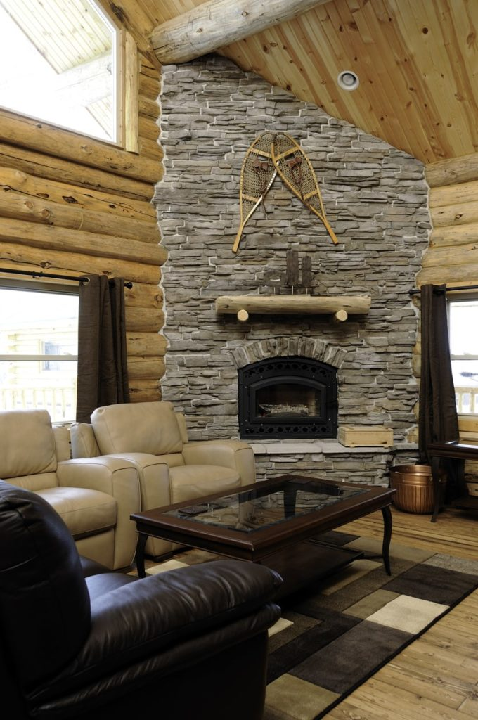 A living room with leather seats and a classy center table set on a stylish rug covering the hardwood flooring. The room also offers a large stone fireplace.