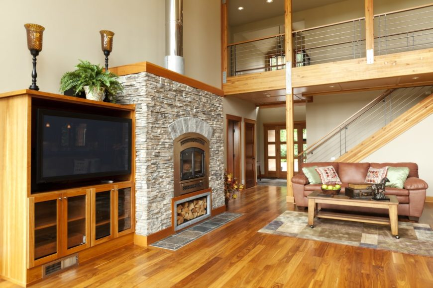A spacious living room featuring a widescreen TV, a fireplace and a leather couch. The area has two-story ceiling and hardwood flooring.