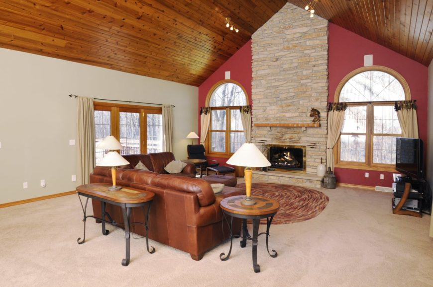 This living room boasts white carpet flooring and a wooden vaulted ceiling, along with white and red walls and a fireplace.