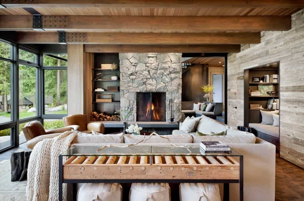 This living room boasts a charming fireplace and a wooden ceiling with exposed beams, along with glass windows overlooking the calming outdoor views.