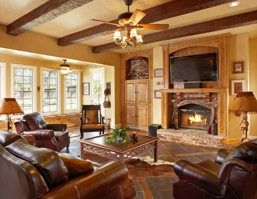 Large living room with brown leather seats and a stunning flooring, along with a large fireplace with a TV on top.