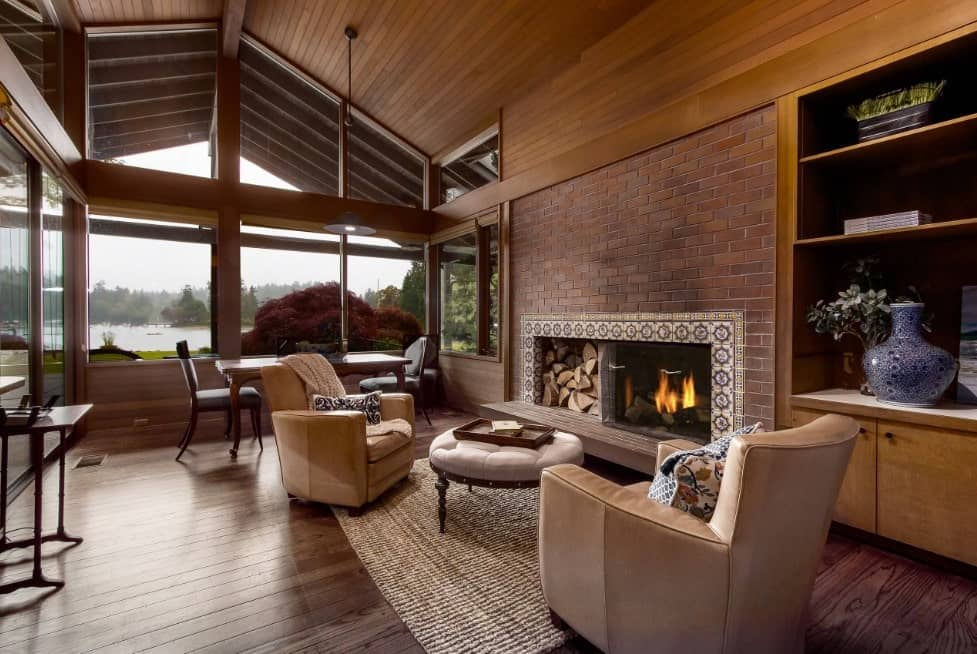 Large formal living space featuring classy seats set near the fireplace. The room has hardwood flooring matching the wooden ceiling.