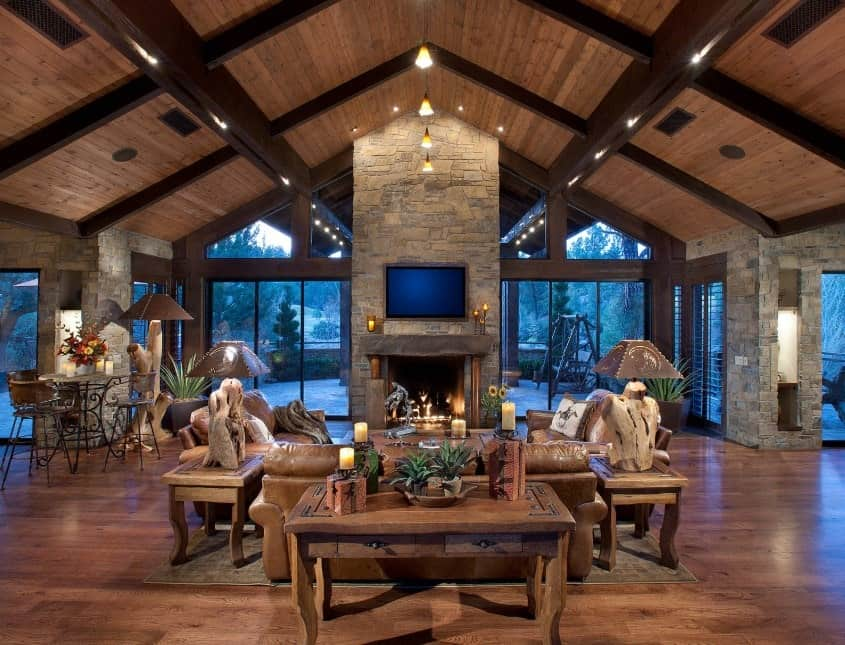 Large formal living room with brown leather seats that look perfect together with the rustic side tables and flooring. The vaulted ceiling looks magnificent.