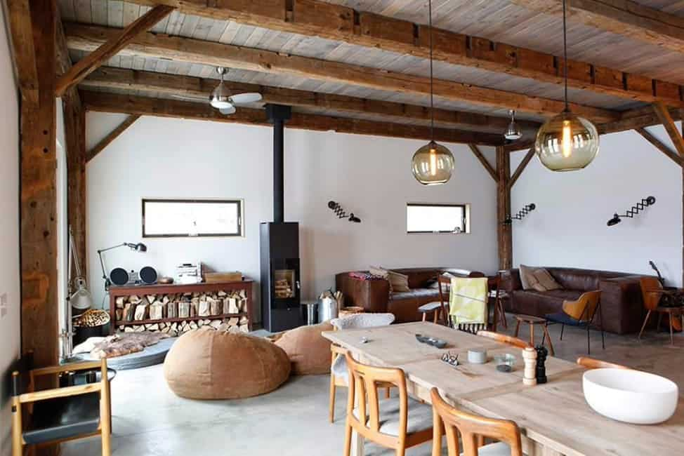 Great room featuring a living space with brown leather seats and a wooden dining table set lighted by pendant lights hanging from the rustic ceiling.