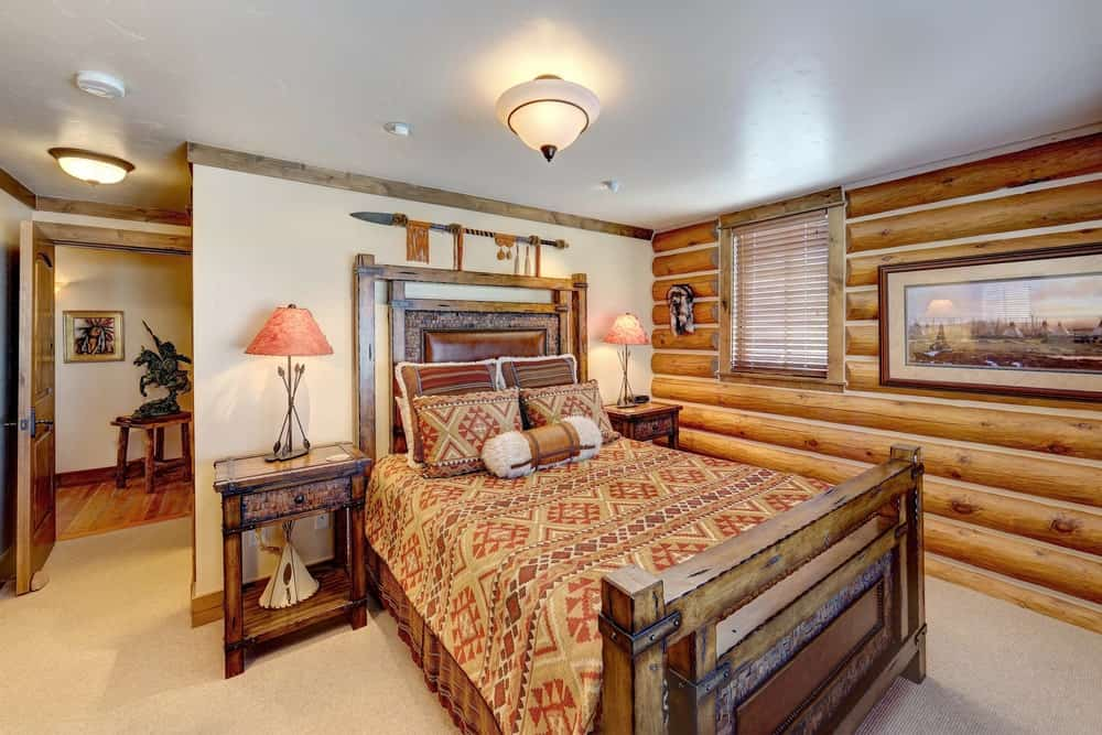 Master bedroom featuring carpet flooring and a rustic wall, along with a rustic bed that is so stylish.