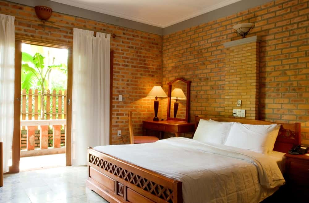 This master bedroom is surrounded by brick tiles walls. It features a large bed with a side table on the left side, while there's a desk lighted by a table lamp on the right side.