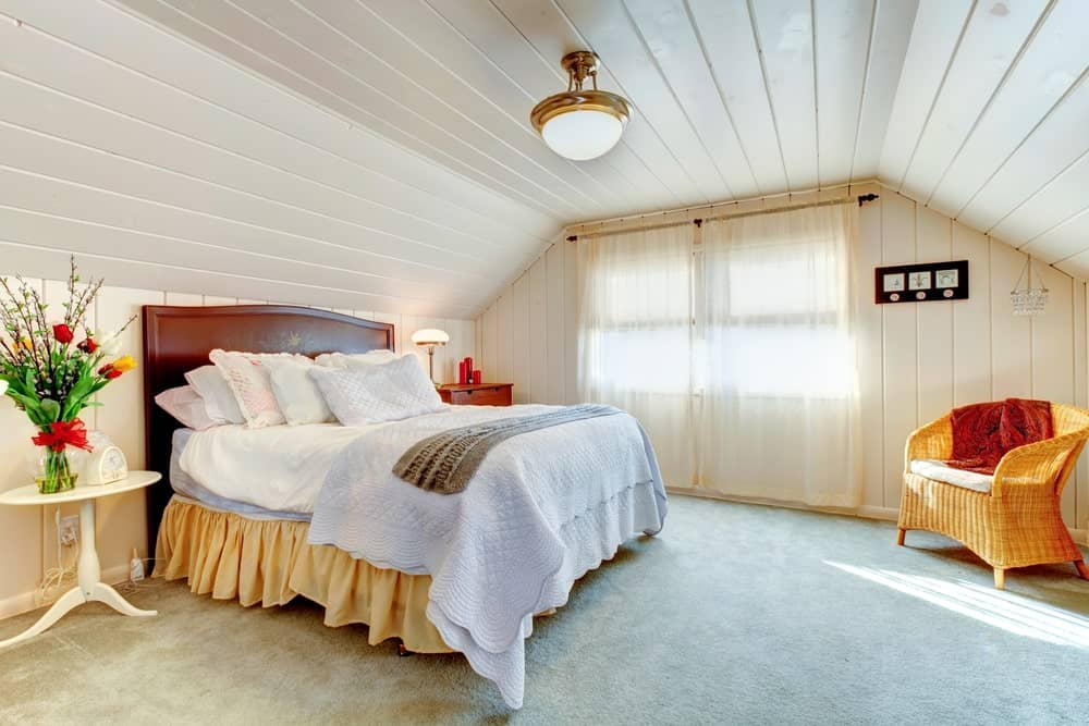 Master bedroom with white hardwood walls and ceiling, along with a large bed set on the carpet flooring.