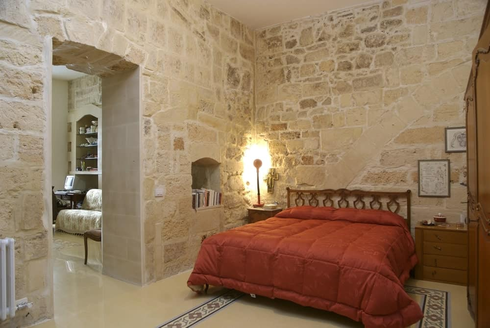This master bedroom has its own living set on the other side. It features stone walls surrounding the bed.