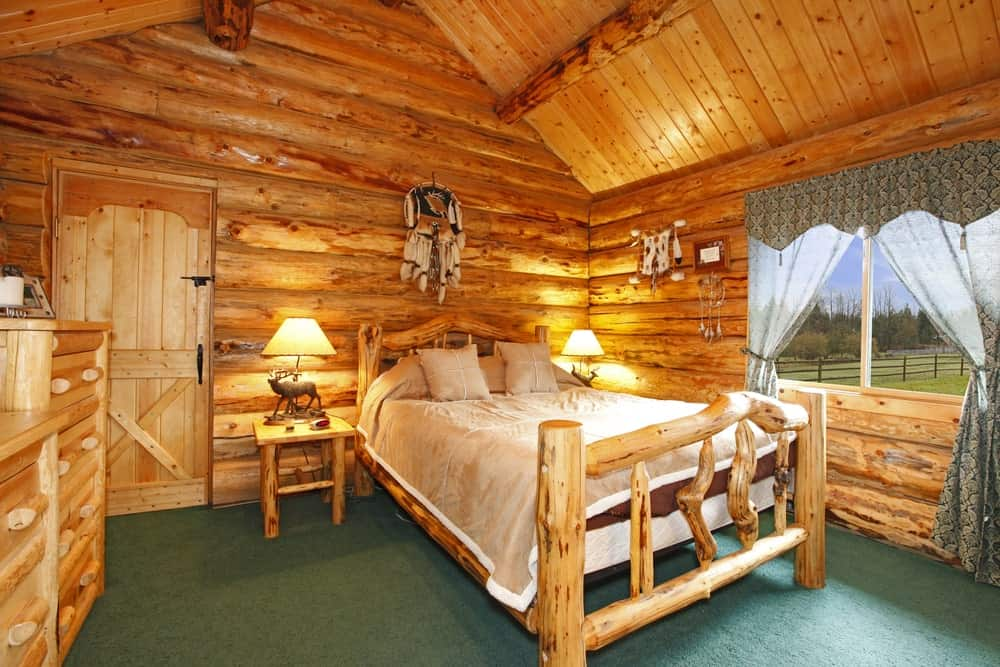 Master bedroom featuring green carpet flooring and rustic walls and ceiling with exposed beams.
