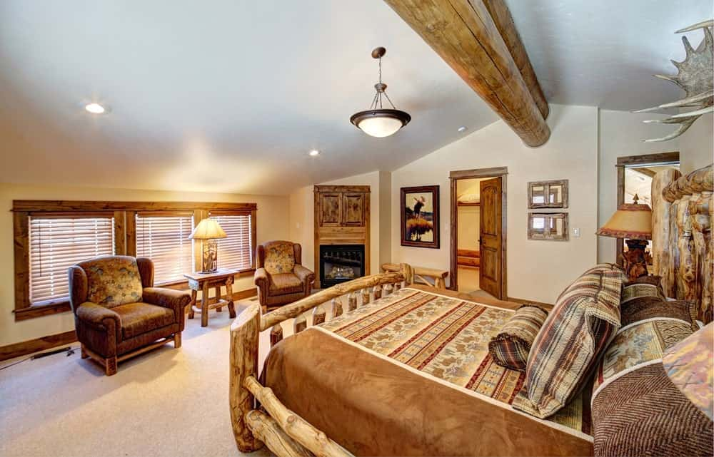 This master bedroom offers a stylish bed along with a sitting area near the fireplace. The room has carpet flooring and a ceiling with a large beam.
