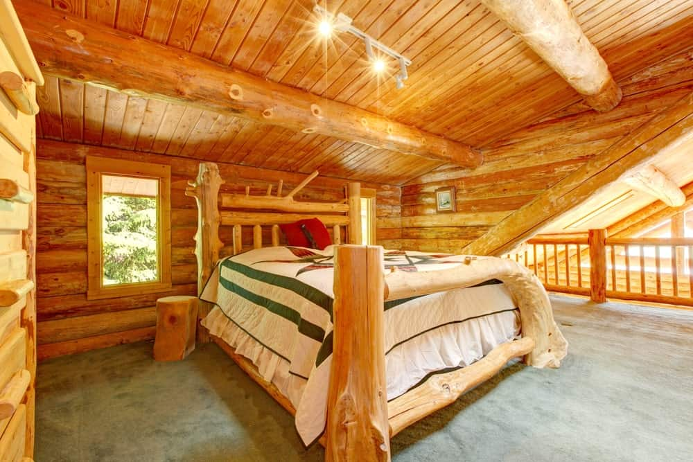 Spacious master bedroom with a large bed set on the carpet flooring. It also features wooden walls and ceiling.